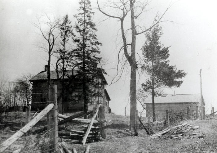 black and white photo of farm and house