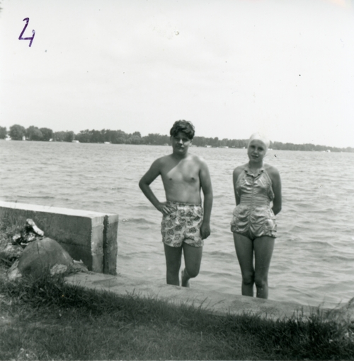 teenage boy and girl standing in lake in swimsuits from the 1950s