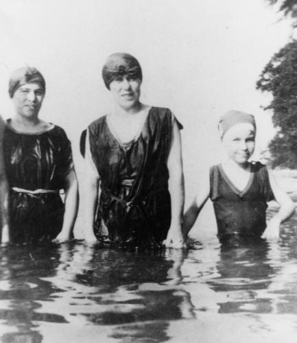 2 women and a girl in old fashioned bathing suits and bathing caps standing waist deep in a lake