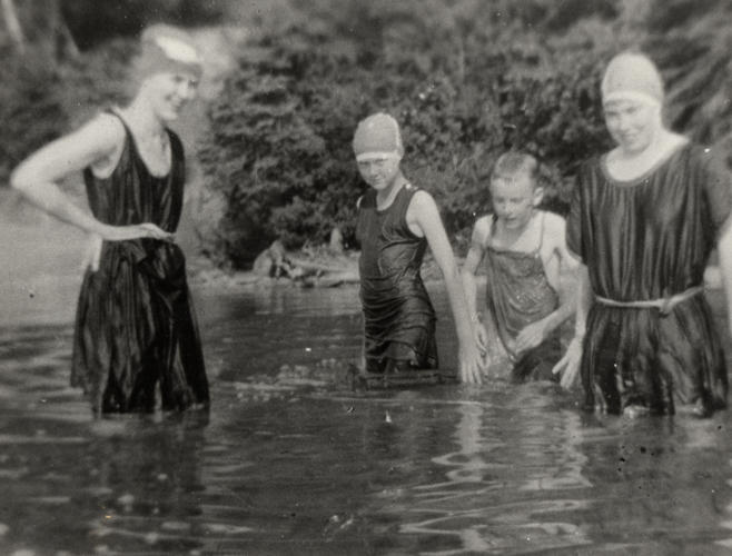 4 people swimming in a lake in old fashioned swimsuits
