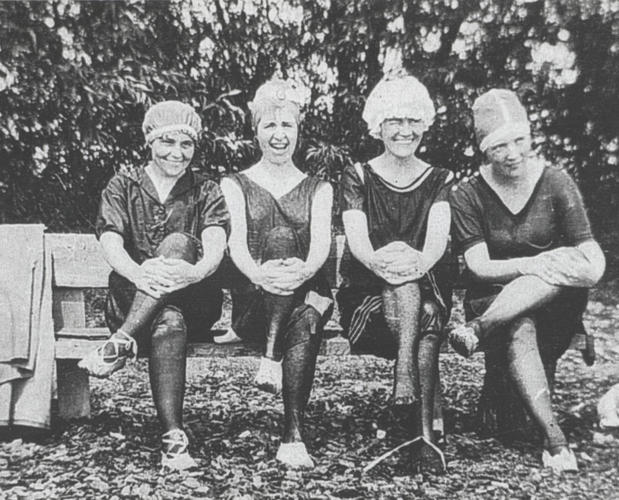 black and white photo of 4 ladies in bathing caps and old fashioned swim suits sitting on a bench