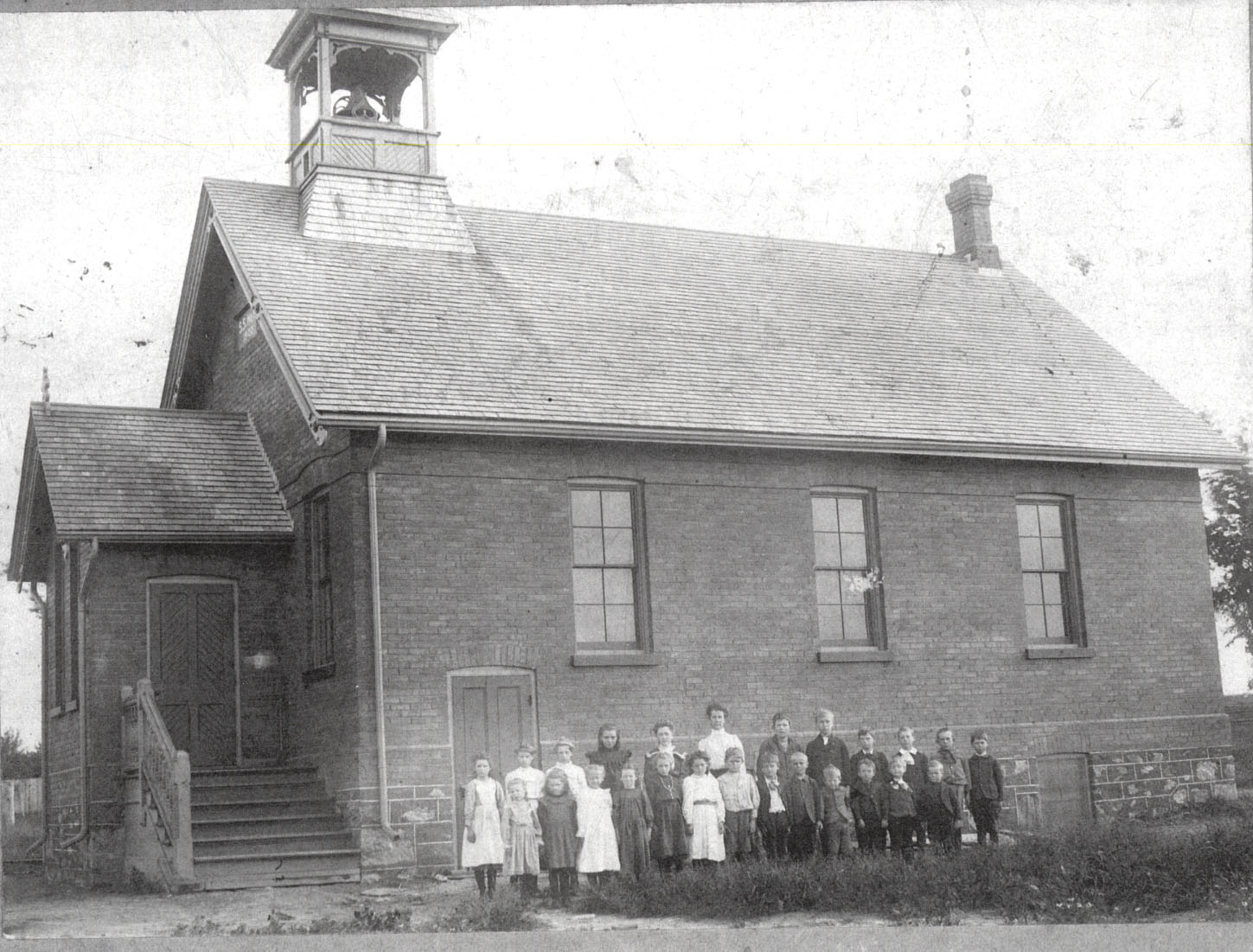 one room school house with close posed outside